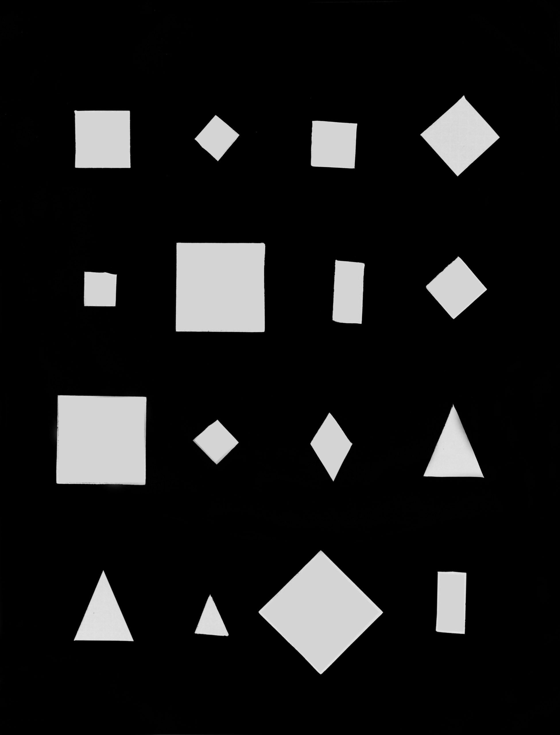 black paper with squares and triangles cut out of it