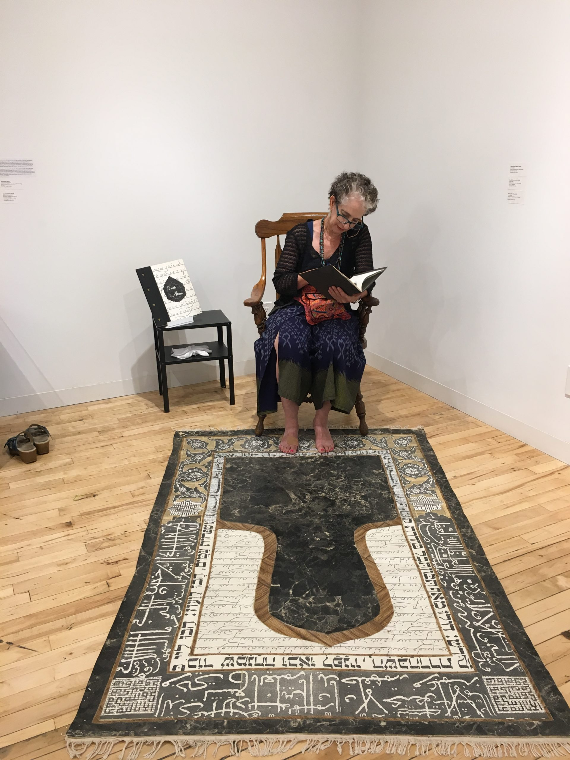 Joyce Dalal sits in a chair reading an artists book with an artwork like islamic style prayer rug laid out before her