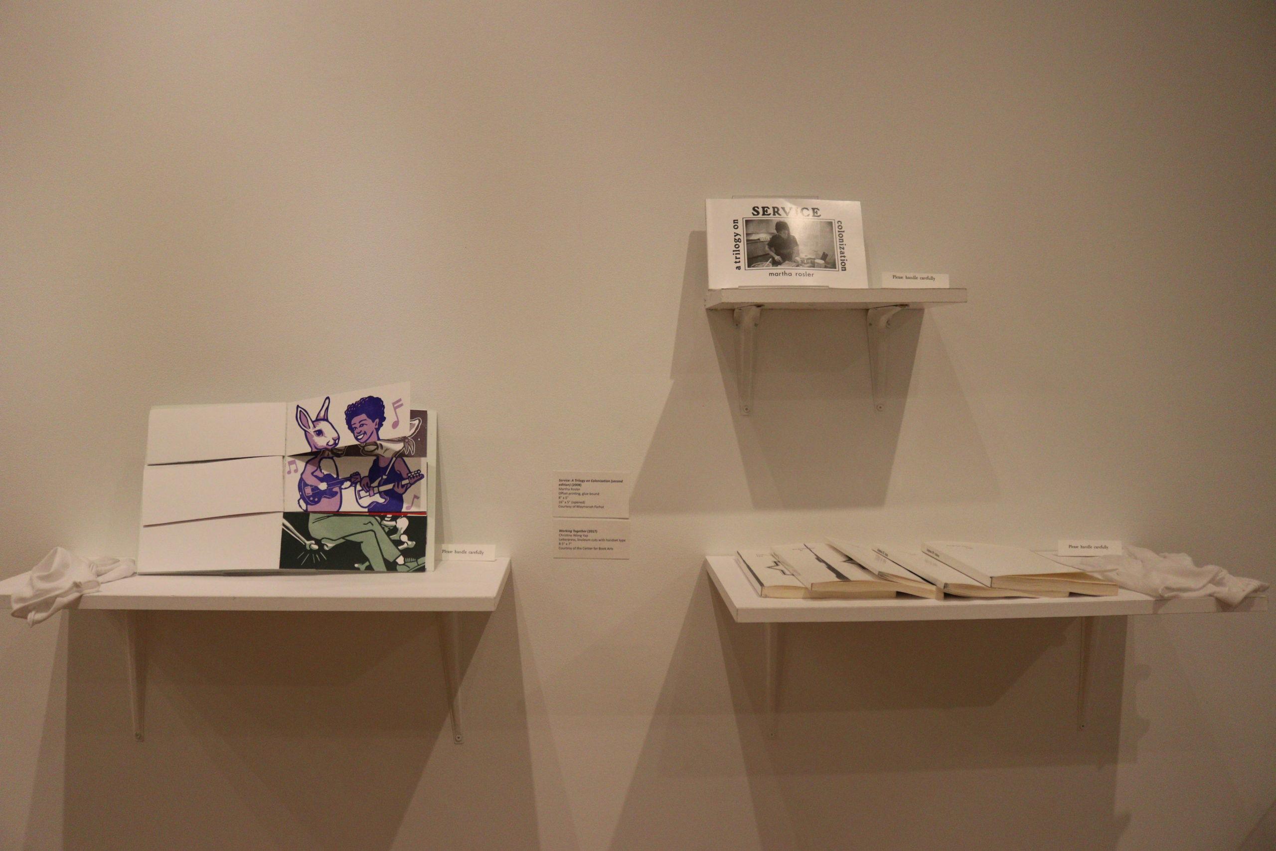 Therr artists books on white shelves