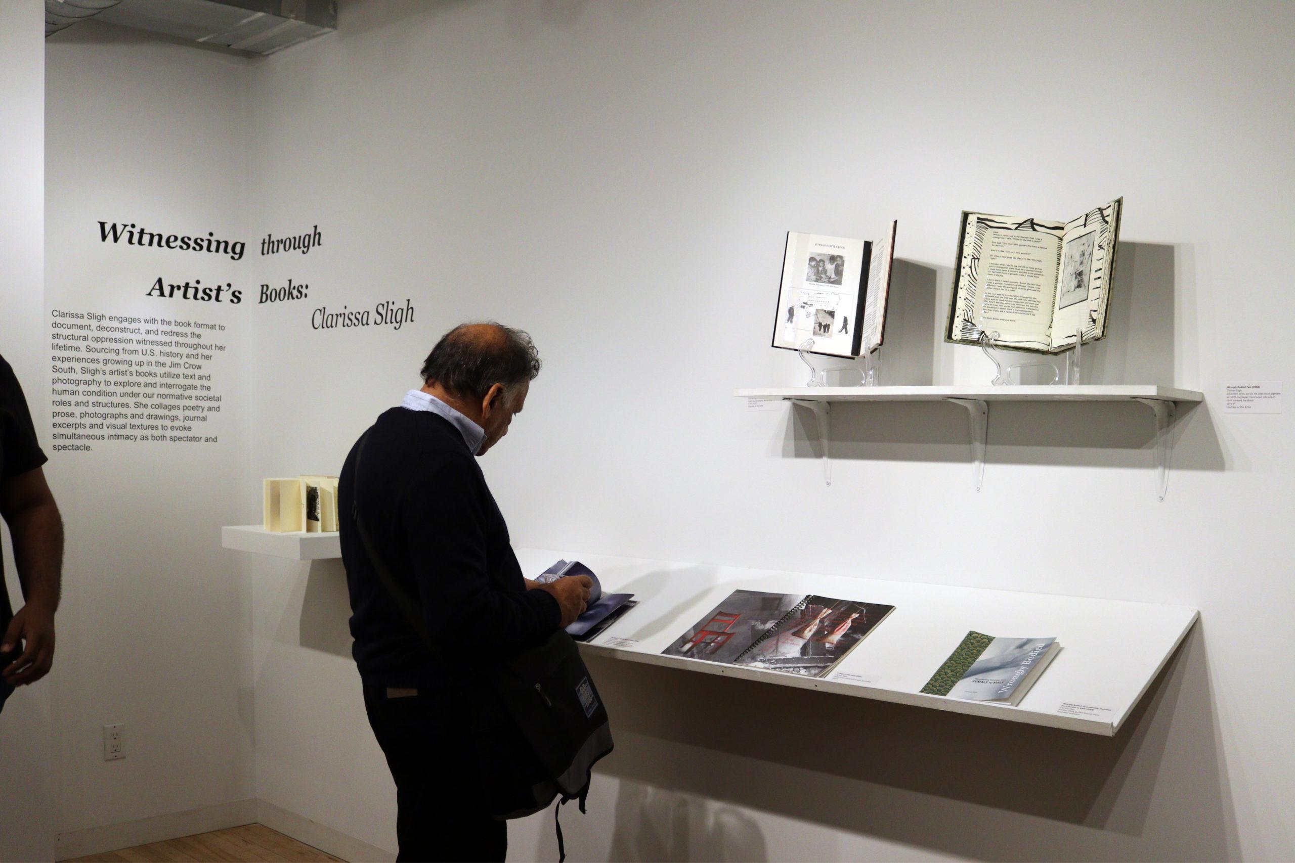 man looks at books by Clarissa Sligh
