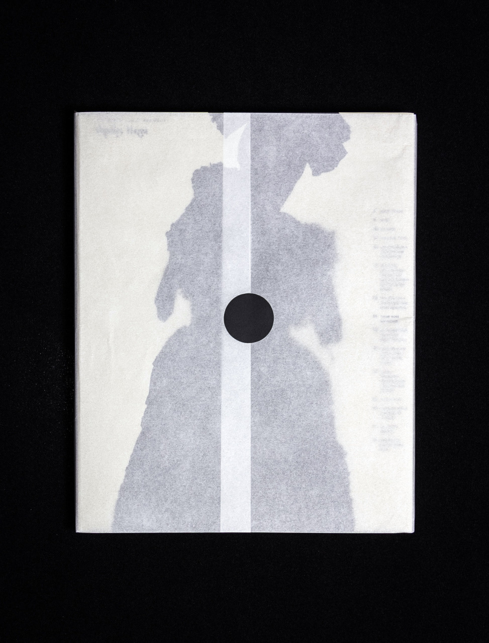 a dark silhouette of a doll on the cover of a book wrapped in translucent paper