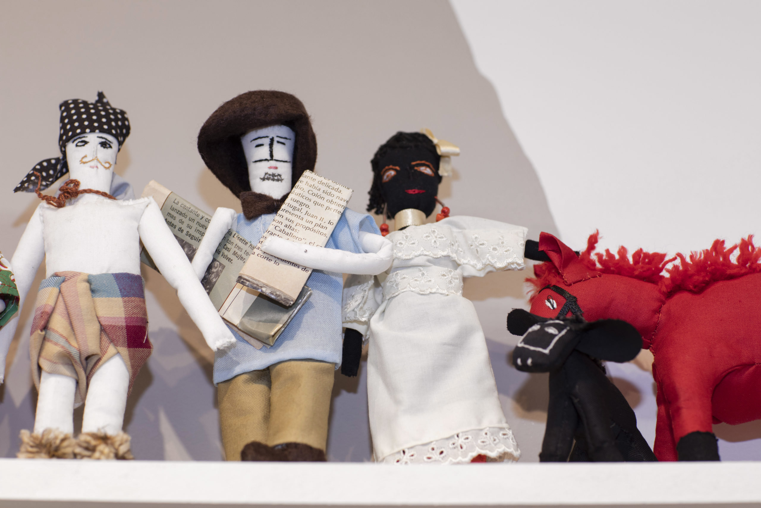 Three rag dolls stand together on a shelf with a small red rag donkey