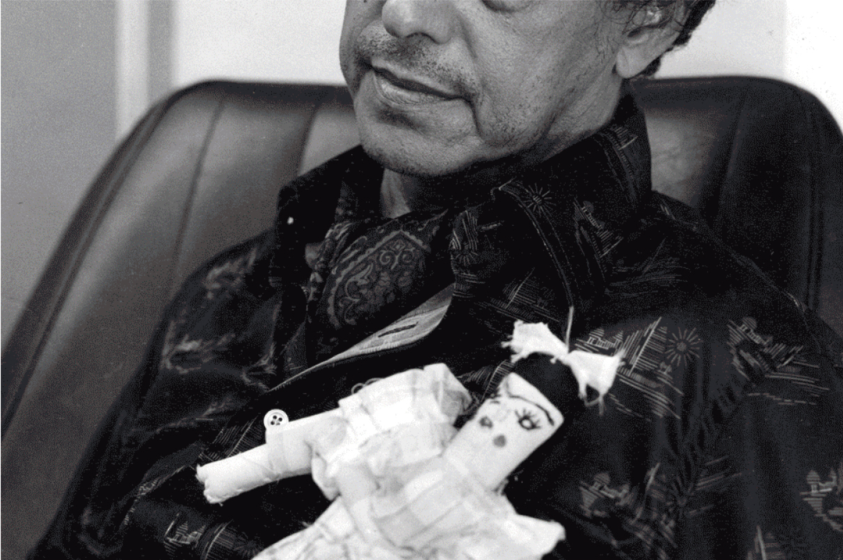 Man holding a rag doll with a little bow in her hair