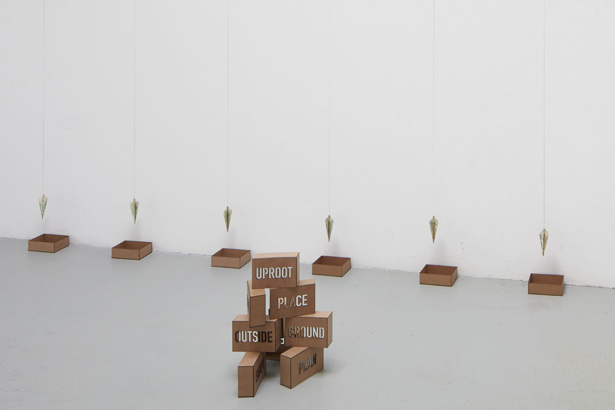 Installation of artwork that resembles a stavk of bricks and hanging plumb lines