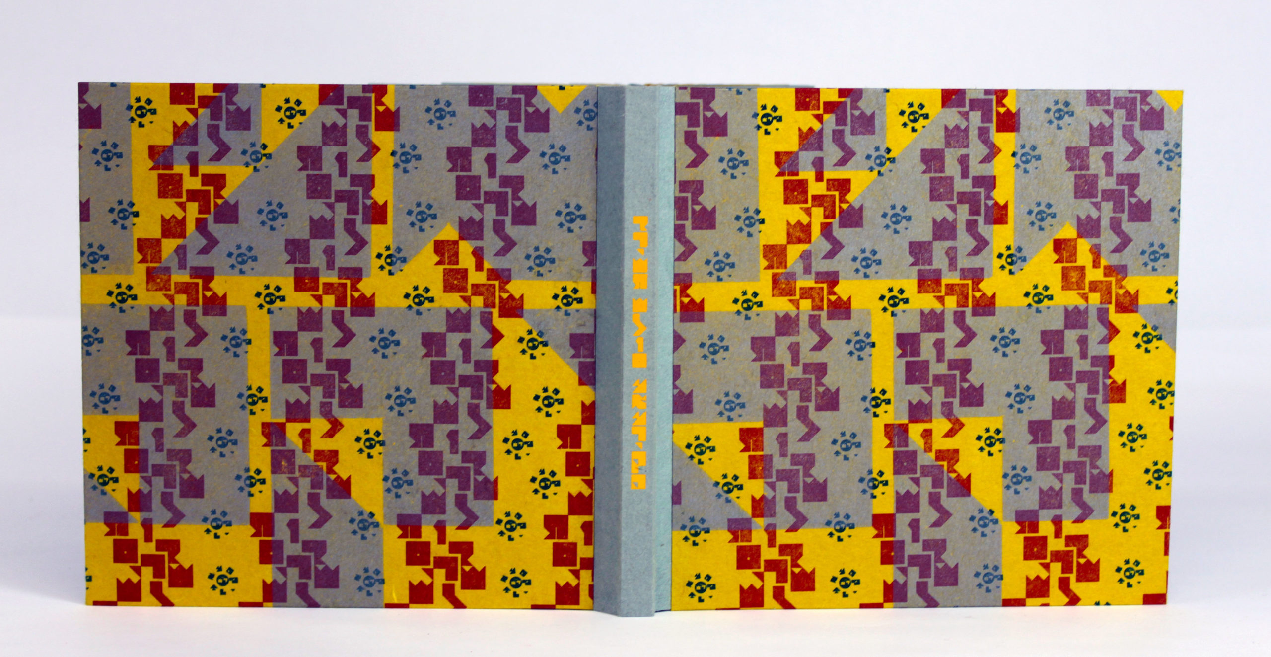 book sitting on its tail showing front and back covers with bright red and blue patterns of abstracted hebrew letters on yellow paper boards