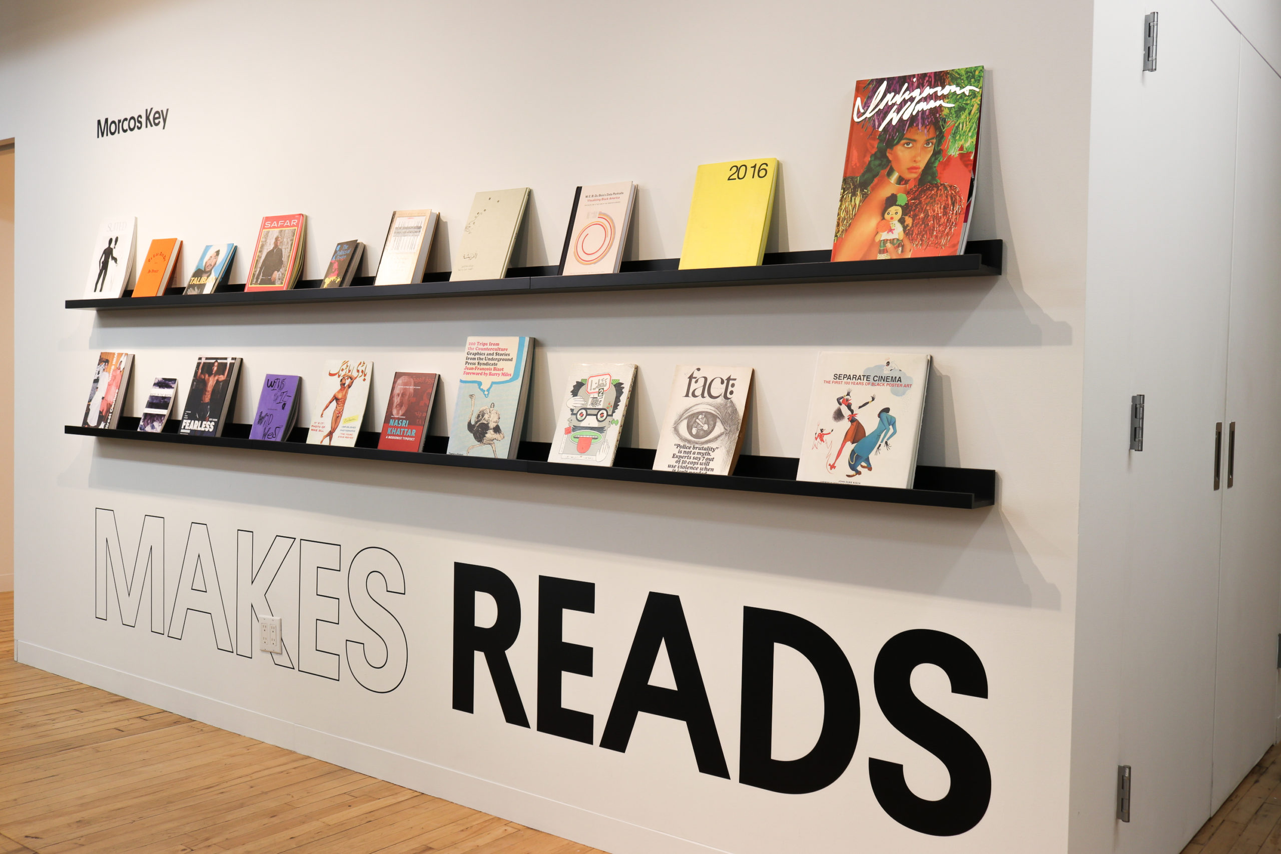 a variety of artists books sit on two shelves