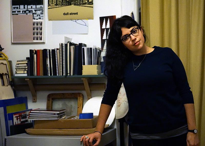 Janine Biunno leans against a desk in her studio