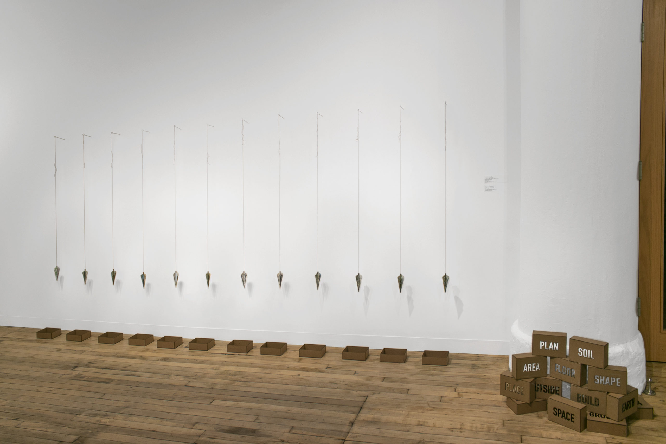 Installation of Viviane Rombaldi Seppey's artwork Way Home, a series of plumb-like books hanging from the wall