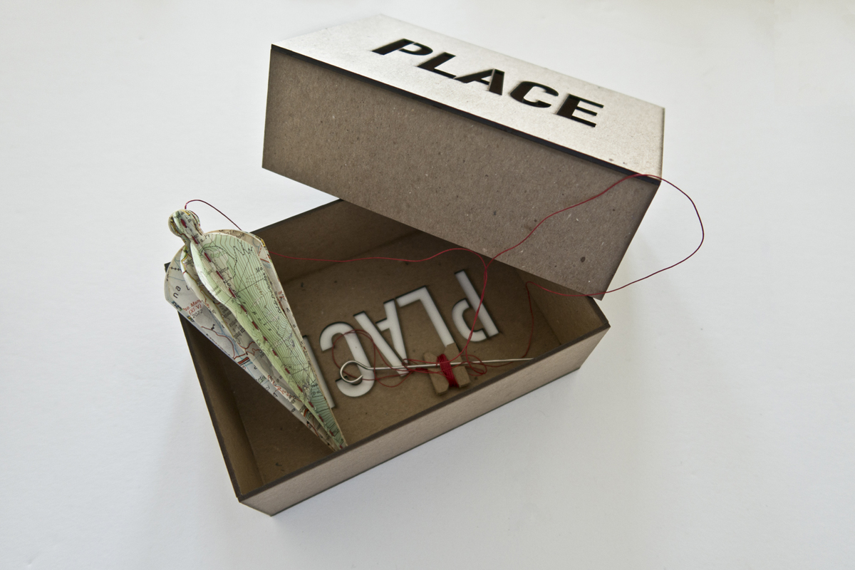 artist's book resembling a carpenters plumb sits inside a box