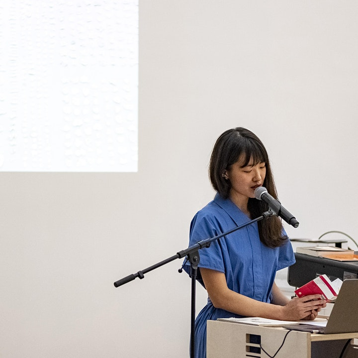 Chan Yuchen stands behind a podium speaking into a microphone