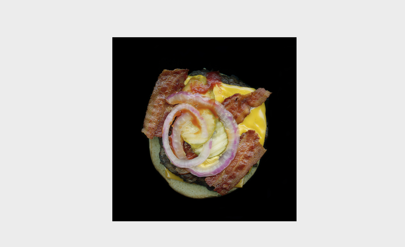 photo of an open face hamburger with bacon, onion, and cheese