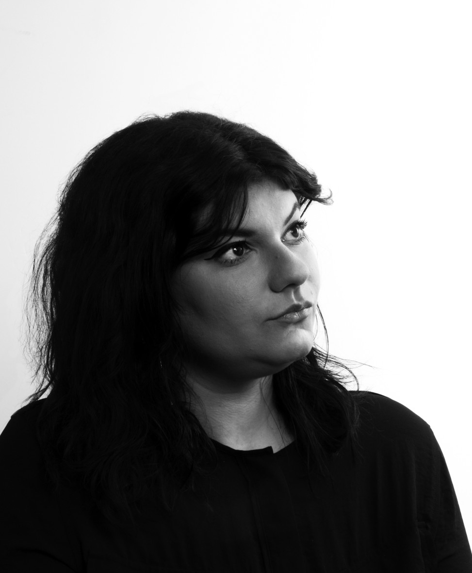 Black and white image of Faride with a white background. She staring off to the right side of the photo.