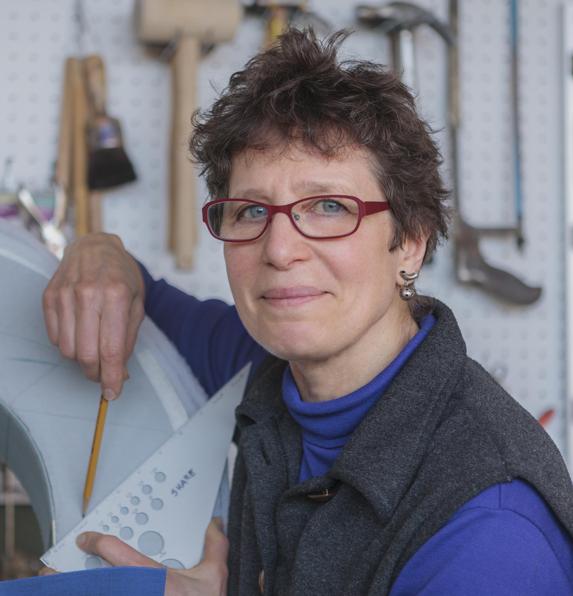 portrait of Susan Joy Share, holding a pencil and a metal triangle.