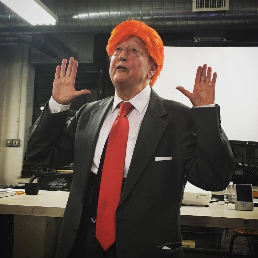 woman wearing orange wig with red tie and hands up