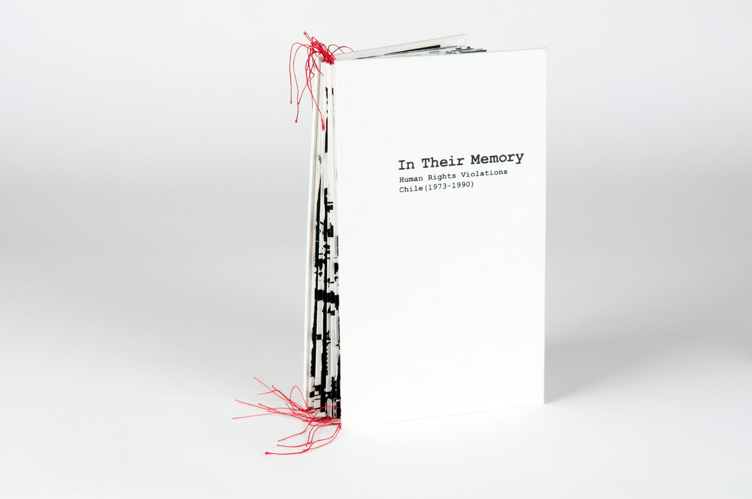 cover of white book with red threads hanging out of the spine