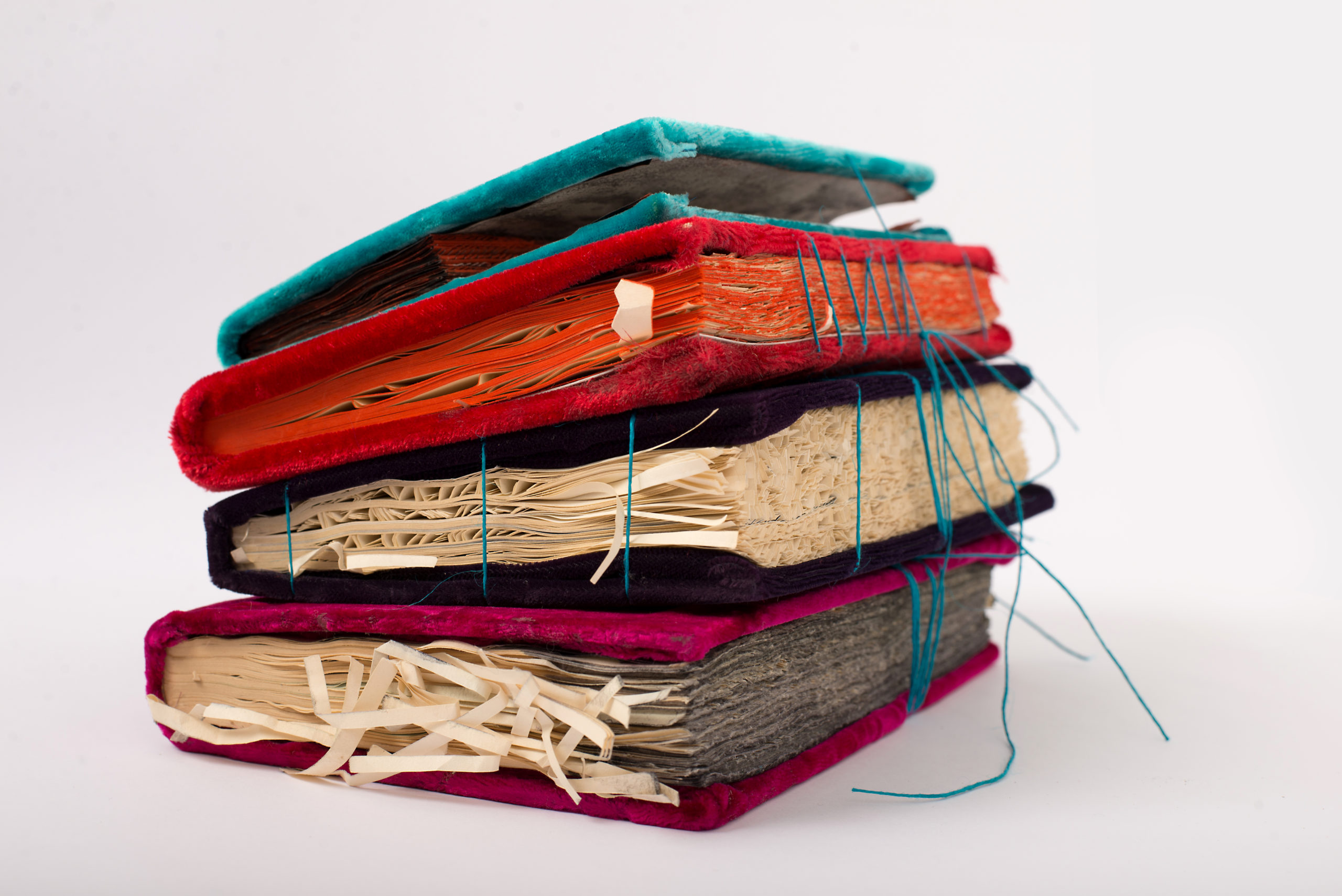 Four books of multiple colors stacked on top of each other, the covers are made of velvet and the pages are frayed. There are teal colored threads coming out of the second book, which is red with orange pages