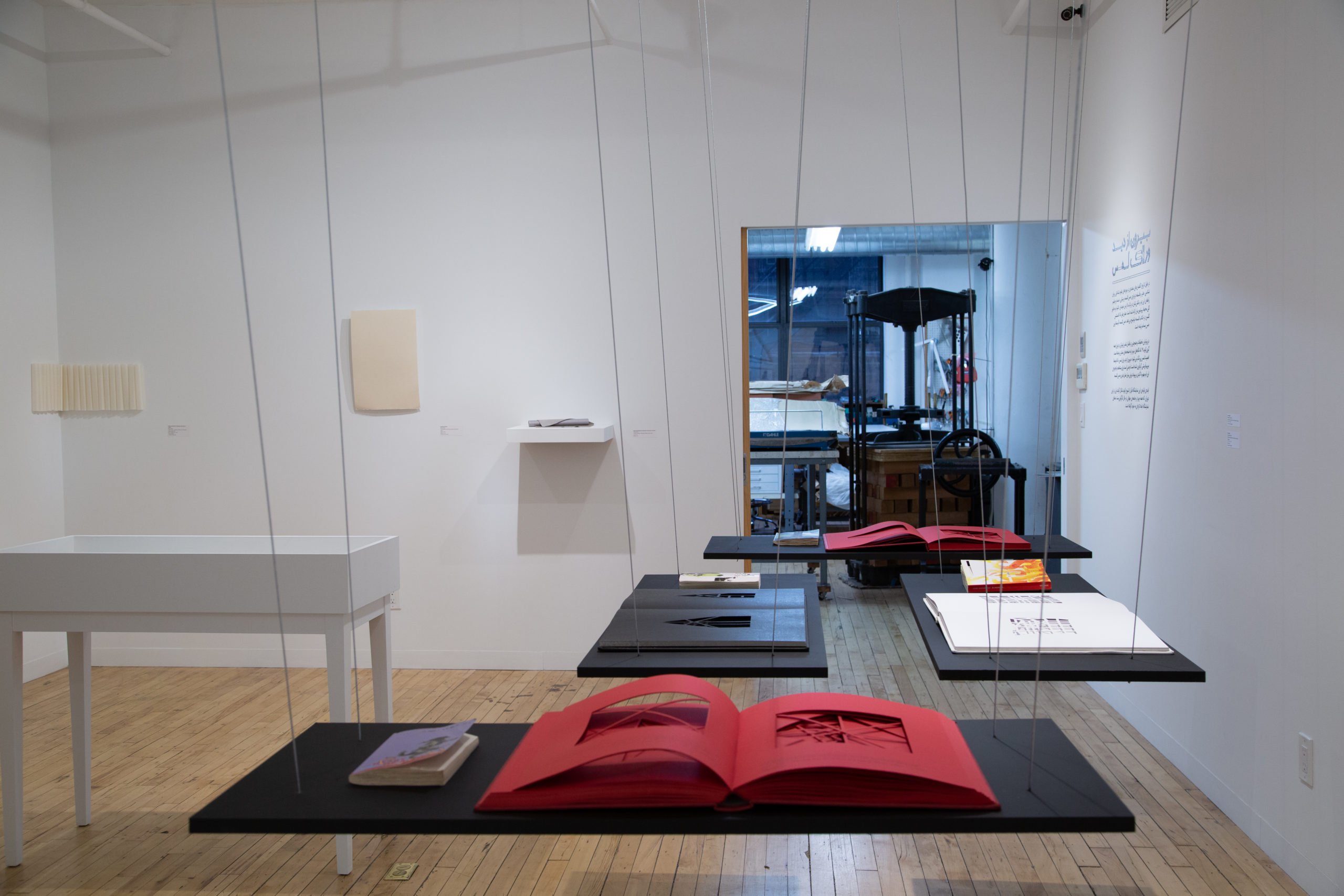 A photo of a large red book opened on a black floating table. The red book has rectangular cutouts. In the background you can see two more floating surfaces with a white book and a black book. The walls are painted white.