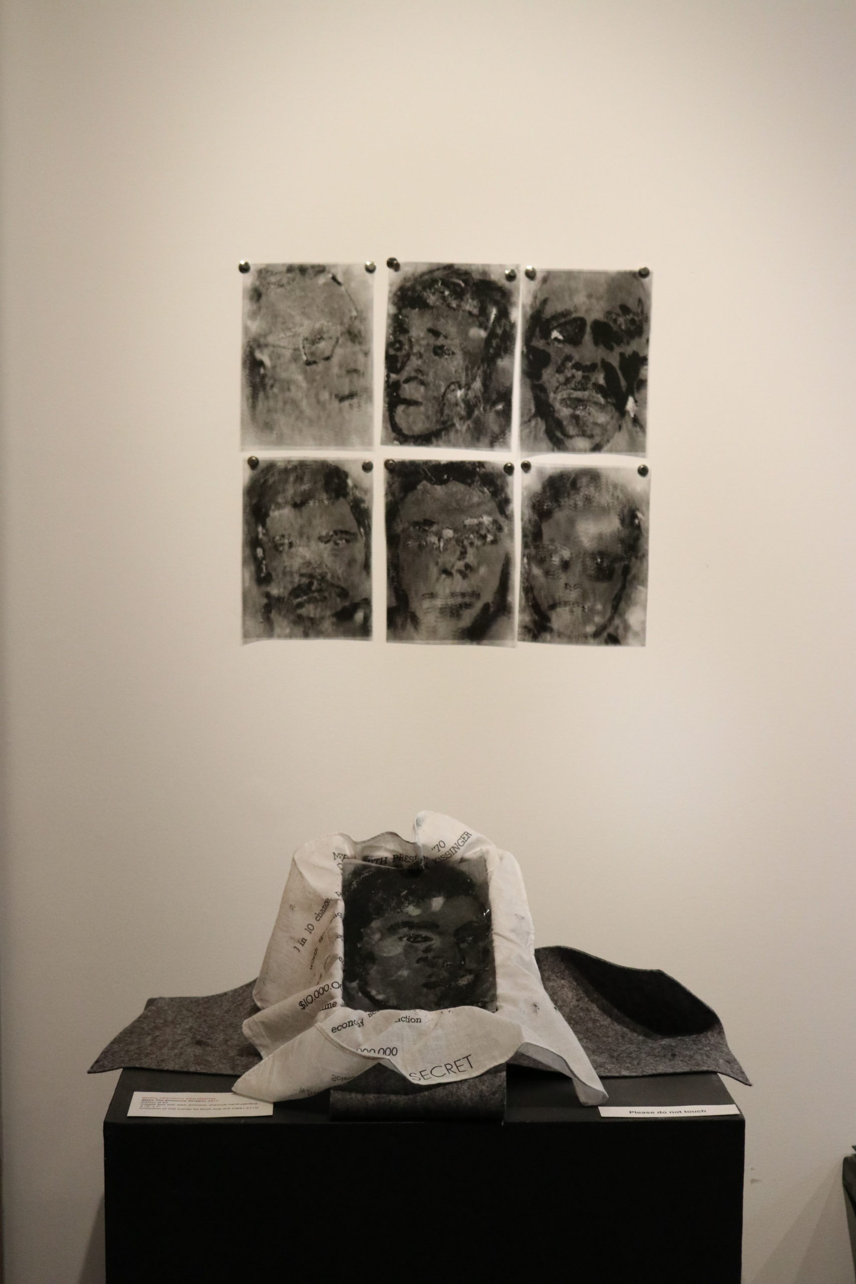 six charcoal paintings of faces on plastic