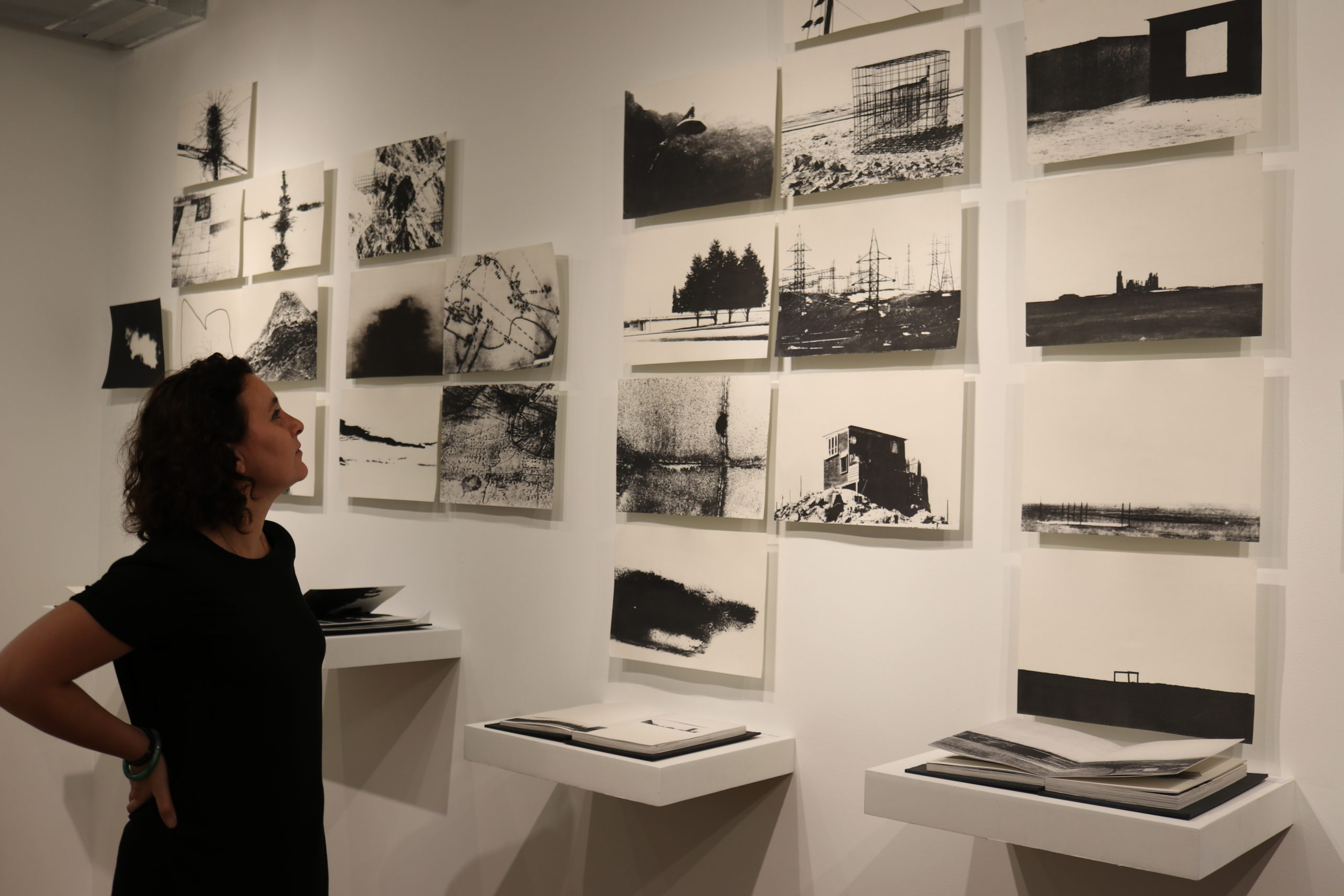 woman looks at a grid on black and white photos