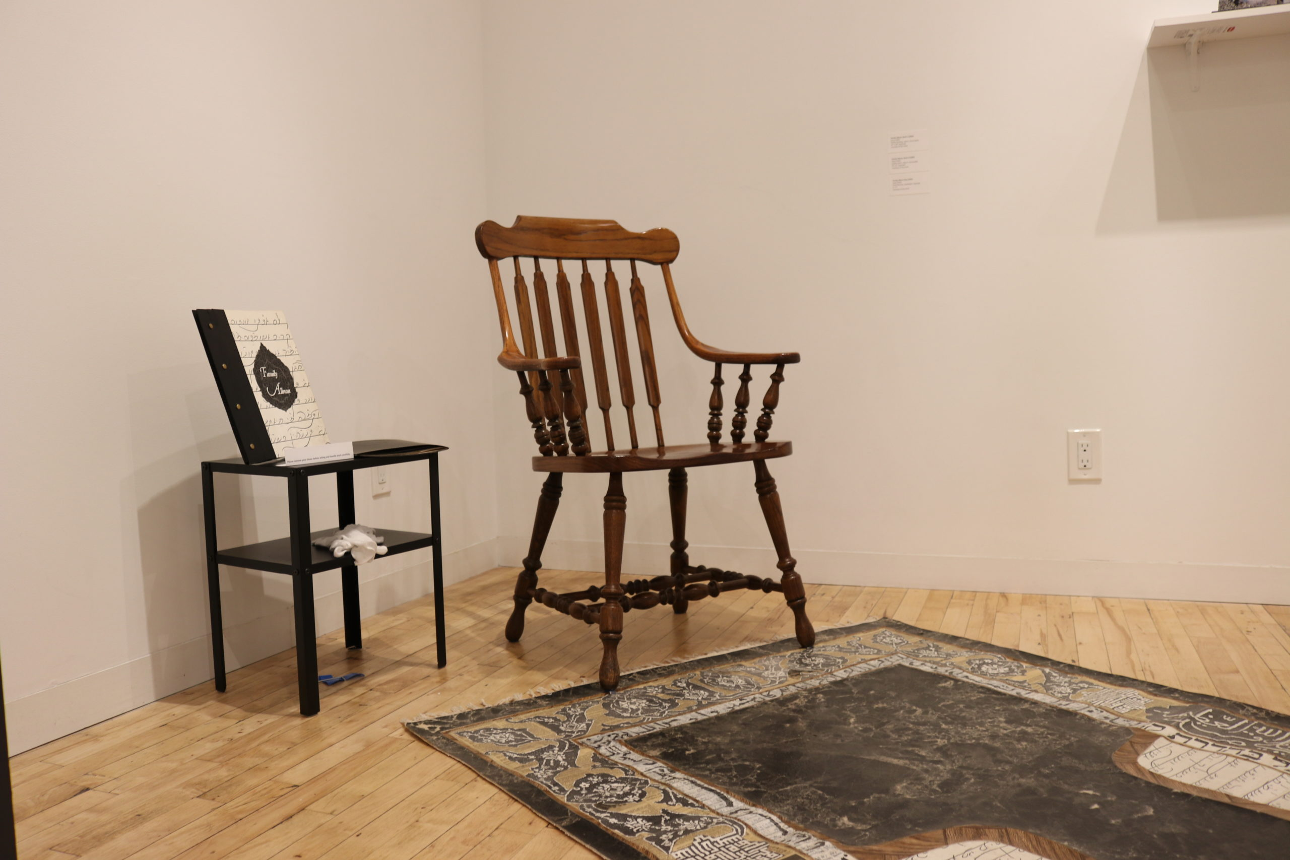 a chair and night stand sit in the corner of the gallery with a rug-like artwork on the floor in front of them