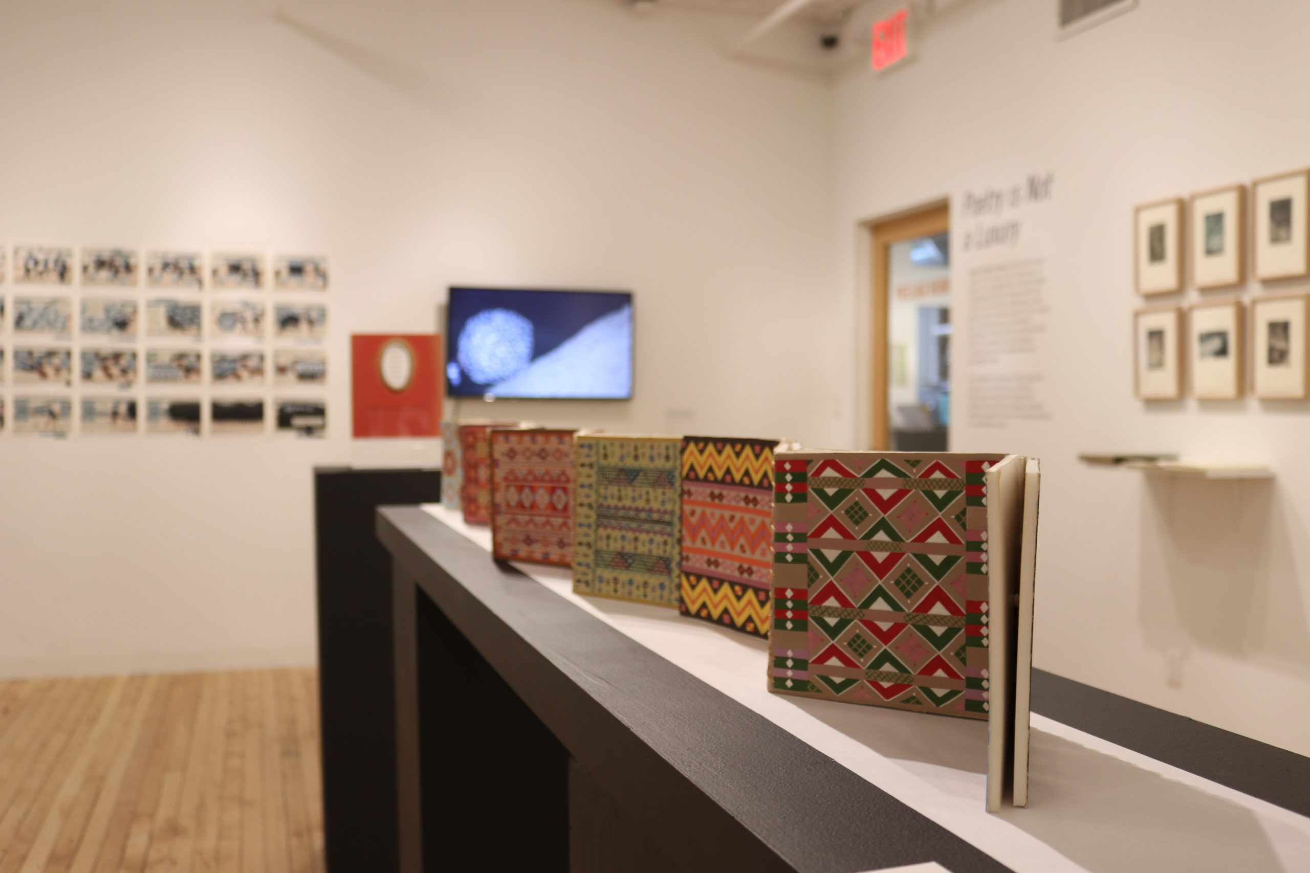 a long accordion book with brightly colored intricate patterns stands in the center of the gallery