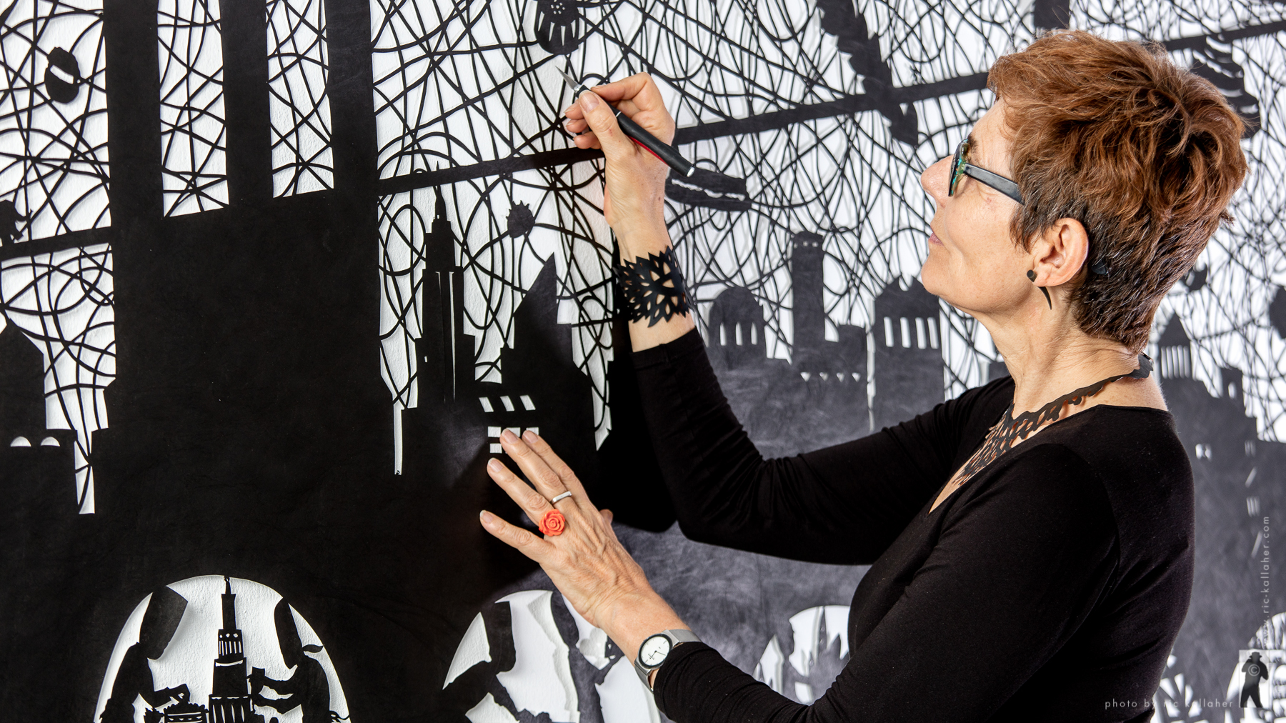 Beatrice working on a large papercut of a city skyline