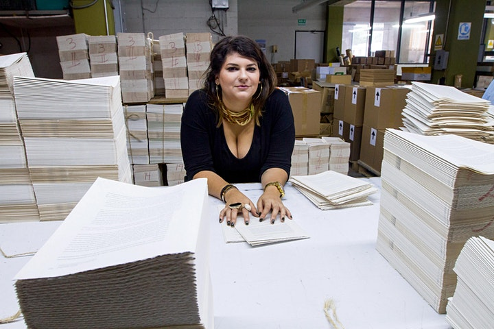Faride Mereb leaning over a table surrounded by papers.