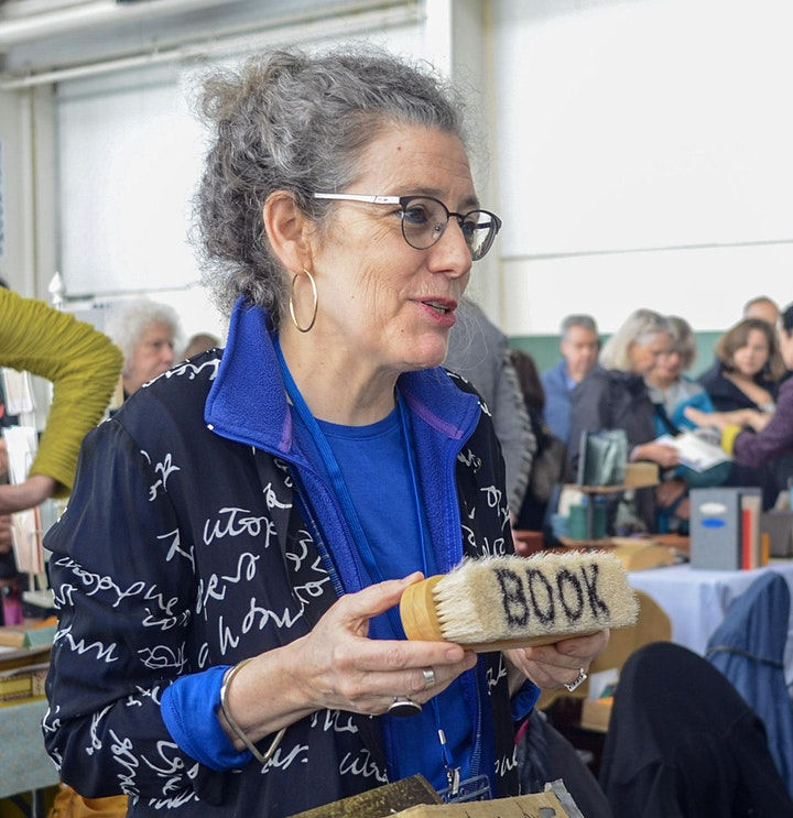 Robbin Ami Silverberg holding a brush that says book