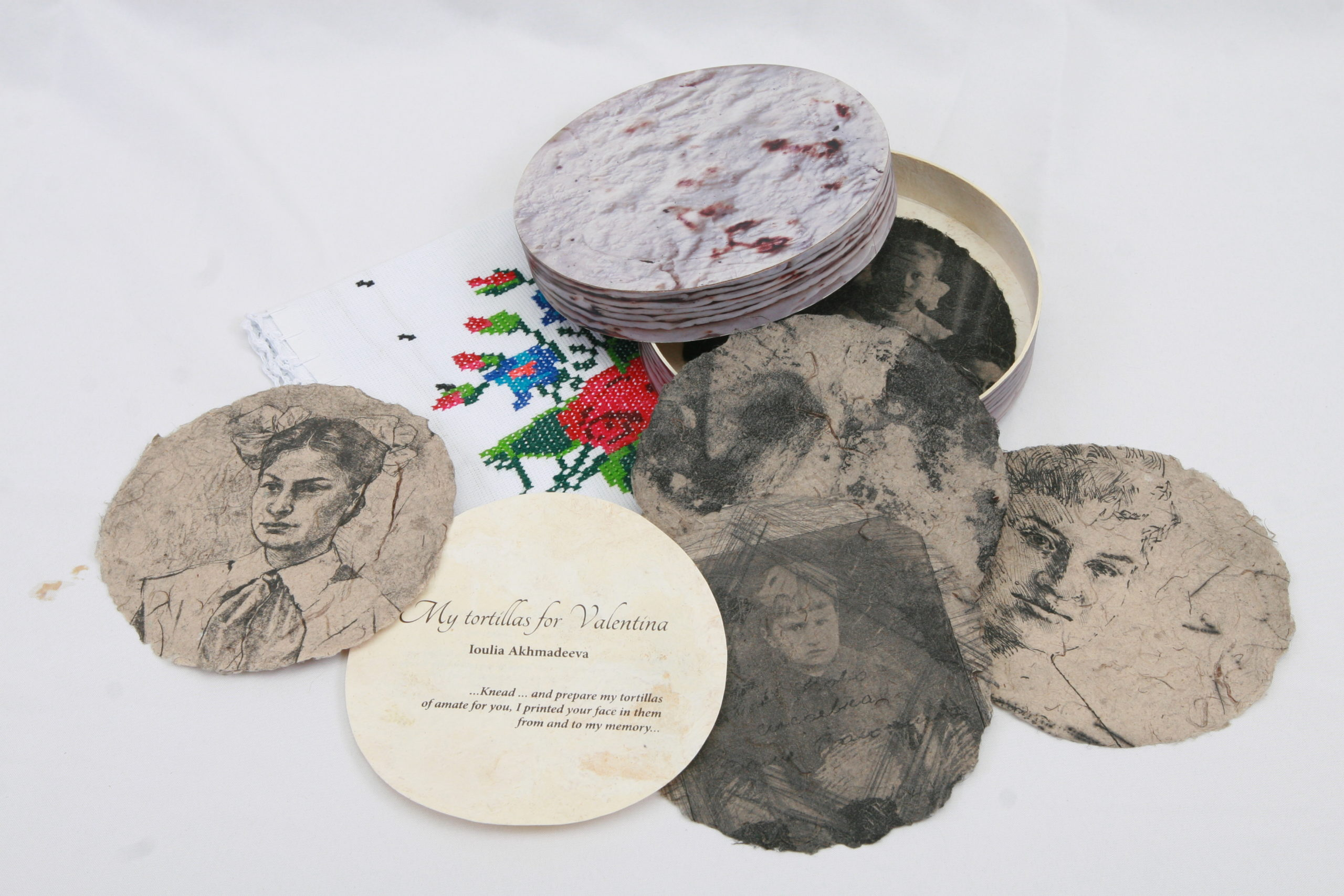 A spread of separate, round paper pages coming out of their circular box