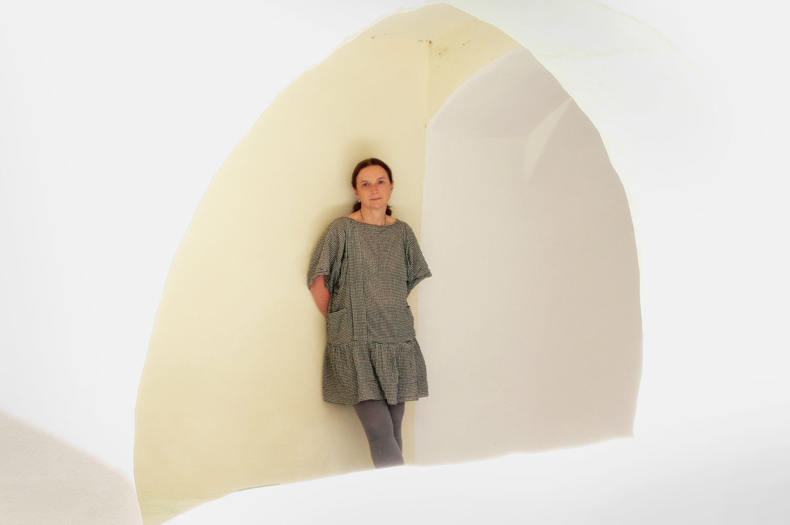 Kikki Ghezzi leans against a wall in a grey dress