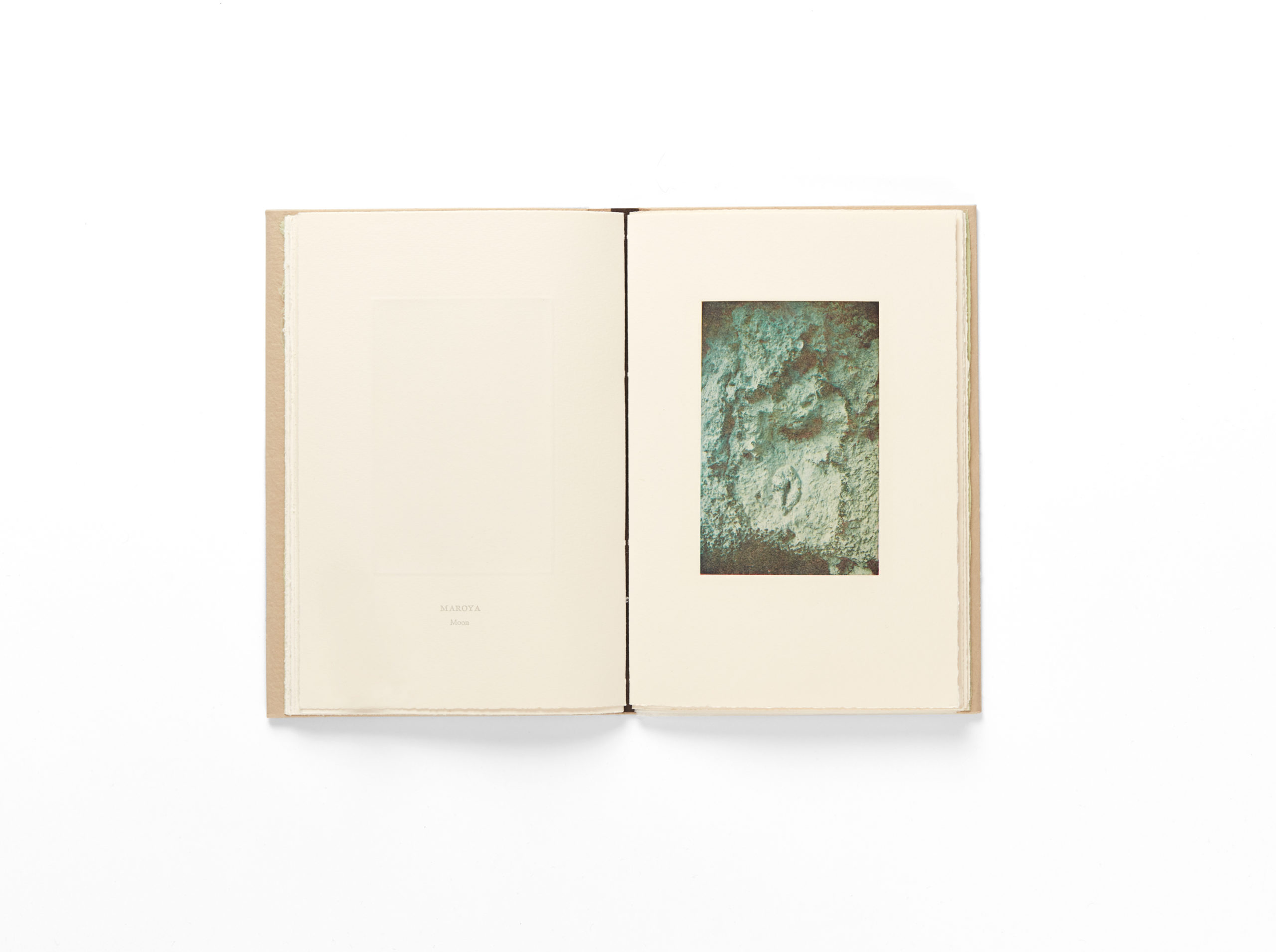 book open to an image of a body shaped recess carved into a rock