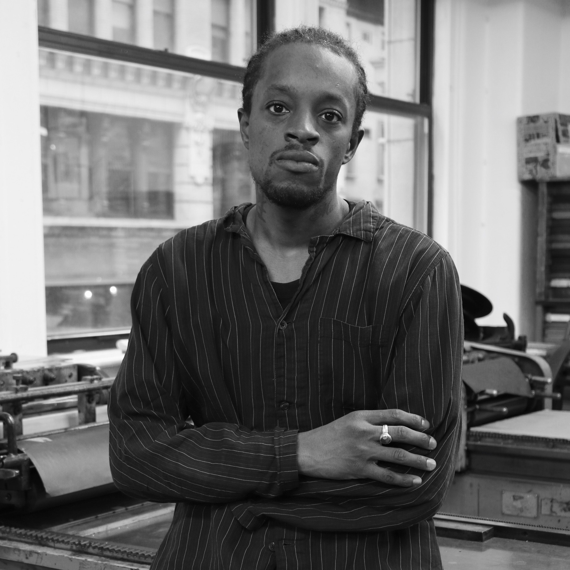 A grayscale photo of a Black man standing with his arms crossed. There is a window behind him.