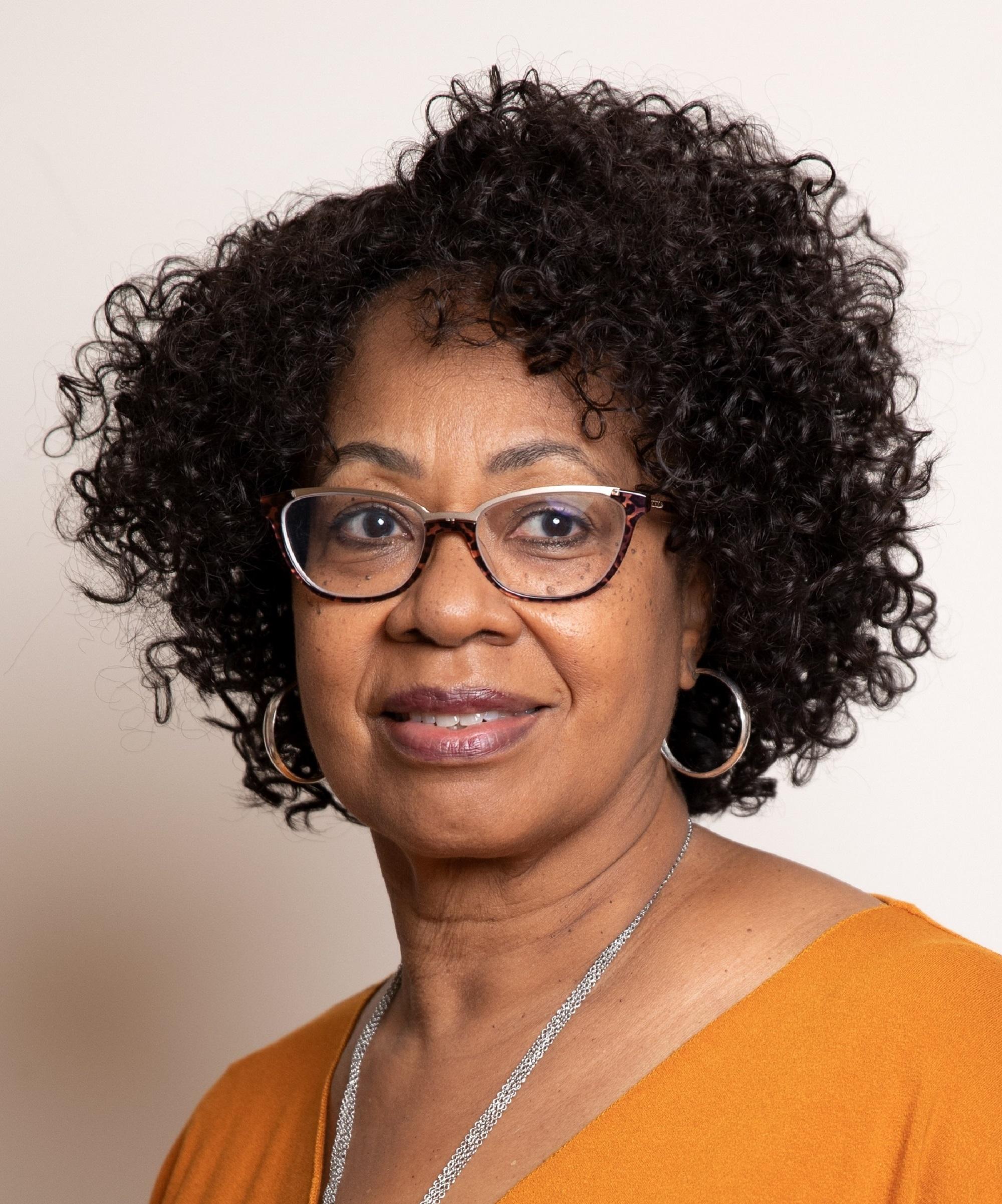 Adjoa Burrowes with dark brown, voluminous curly hair, glasses and hoop earrings