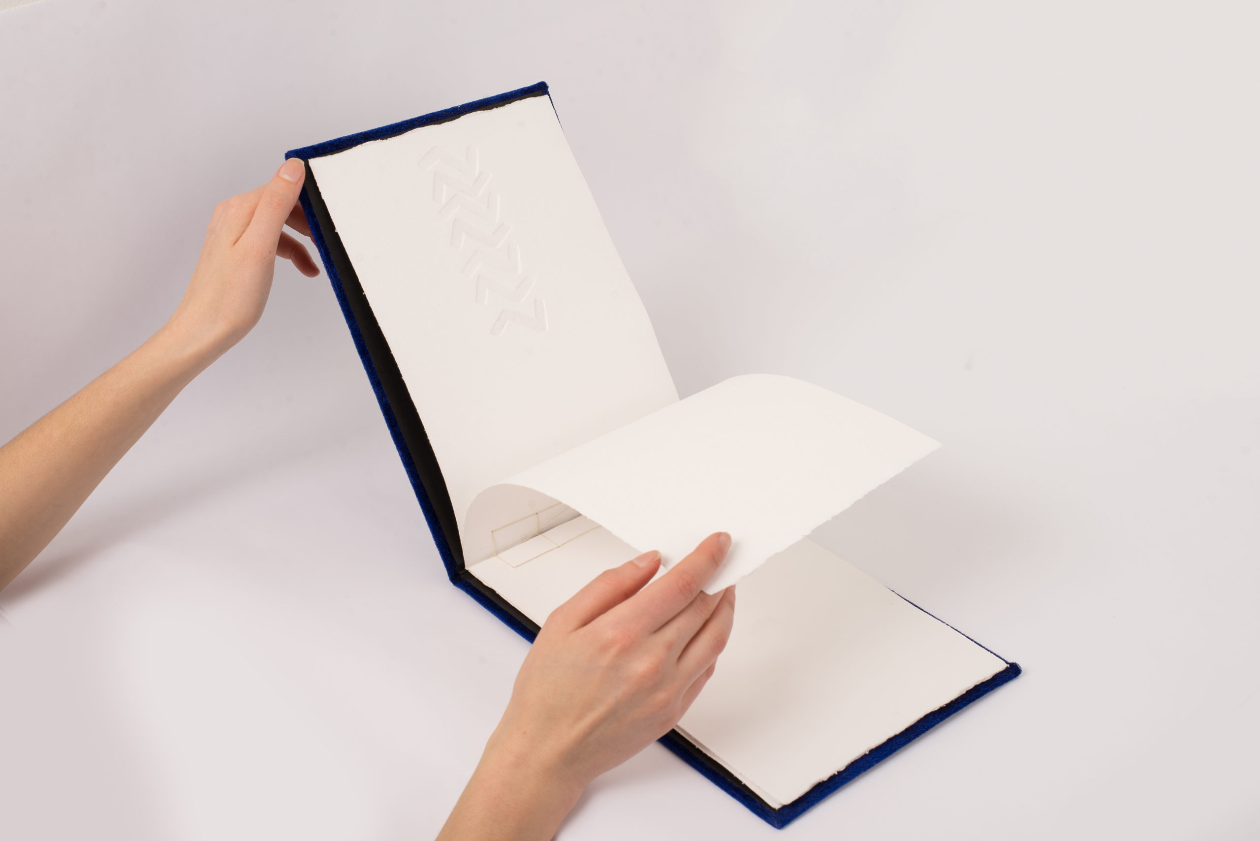 Two pale hands flipping through a wide book with a debossed pattern inside