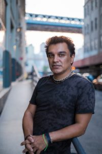 Portrait of Amir Parsa with a cityscape behind him. He is looking directly at the camera