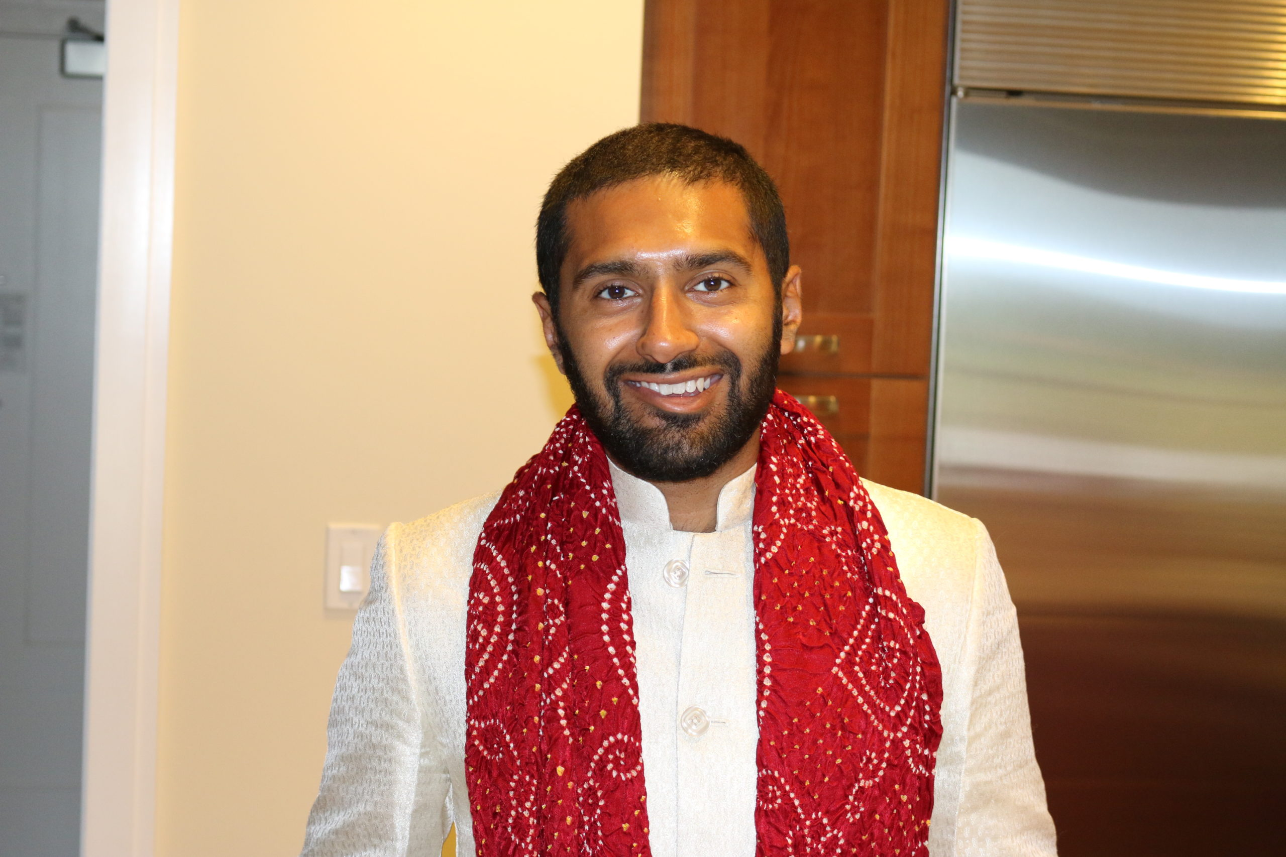 Rushi Vyas with buzzed beard and hair in a white shirt with a red scarf