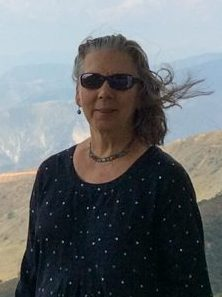 Photo of Barbara Mauriello. She is wearing sunglasses, a necklace, and black shirt and is standing against a background of mountains.