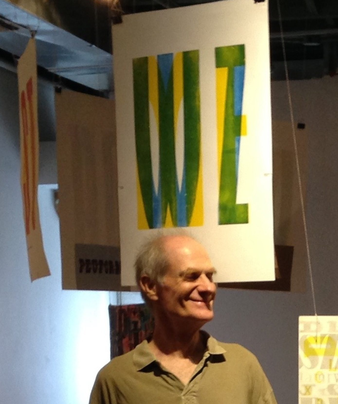 Artist Dikko Faust is standing in a green shirt under a layered letterpress print with misc. letters on it.