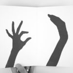 A page spread with two black shillouettes of hands against a white background, failing to properly give a high five