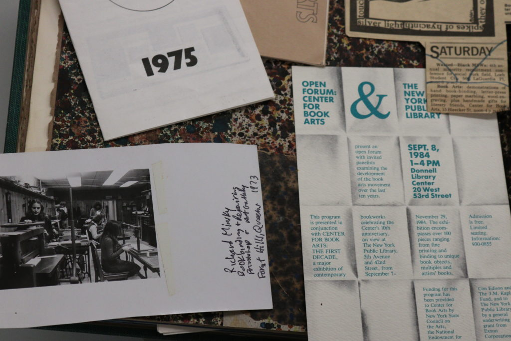 Various images laid out in a scrapbook mapping the Center's first ten years, including a black and white photograph of people working in our bindery, taken by Richard Minsky, and a poster for an open forum in 1984