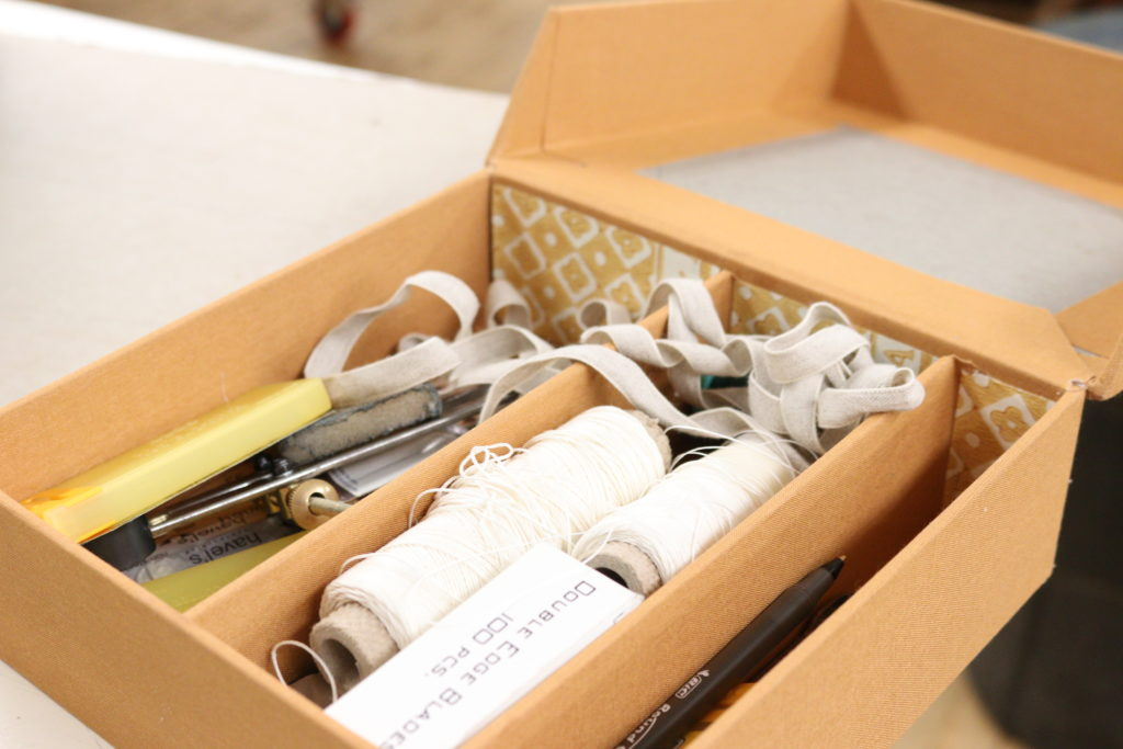 A set of bookbinding materials including thread, an awl, elastics, and needles in a clam shell box
