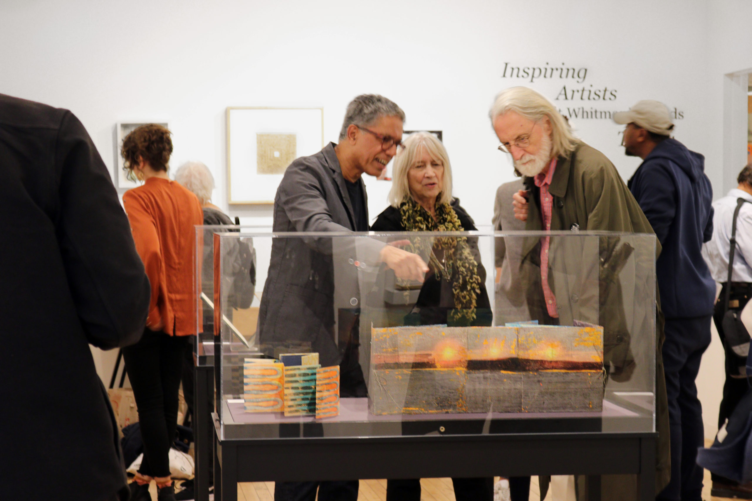 three people gather around an artwork at the center of the gallery
