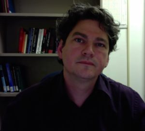 Photo of Mark Paterson looking directly toward the camera. He has a dimly lit bookshelf behind him.