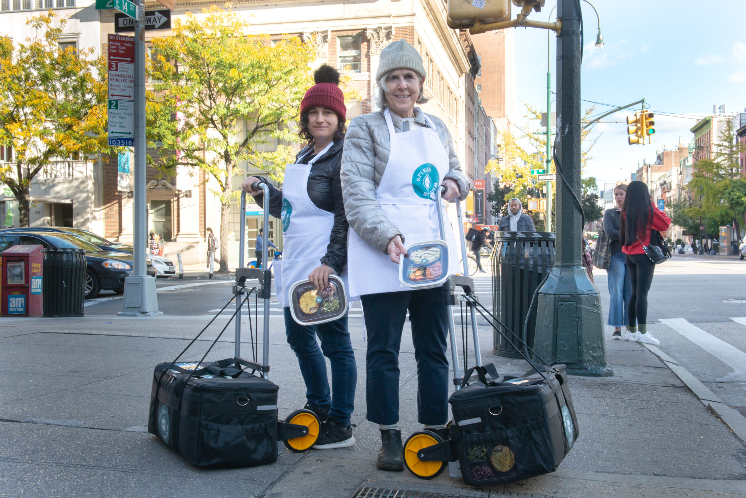 two women with rolly cases in aprons on a sidewalk