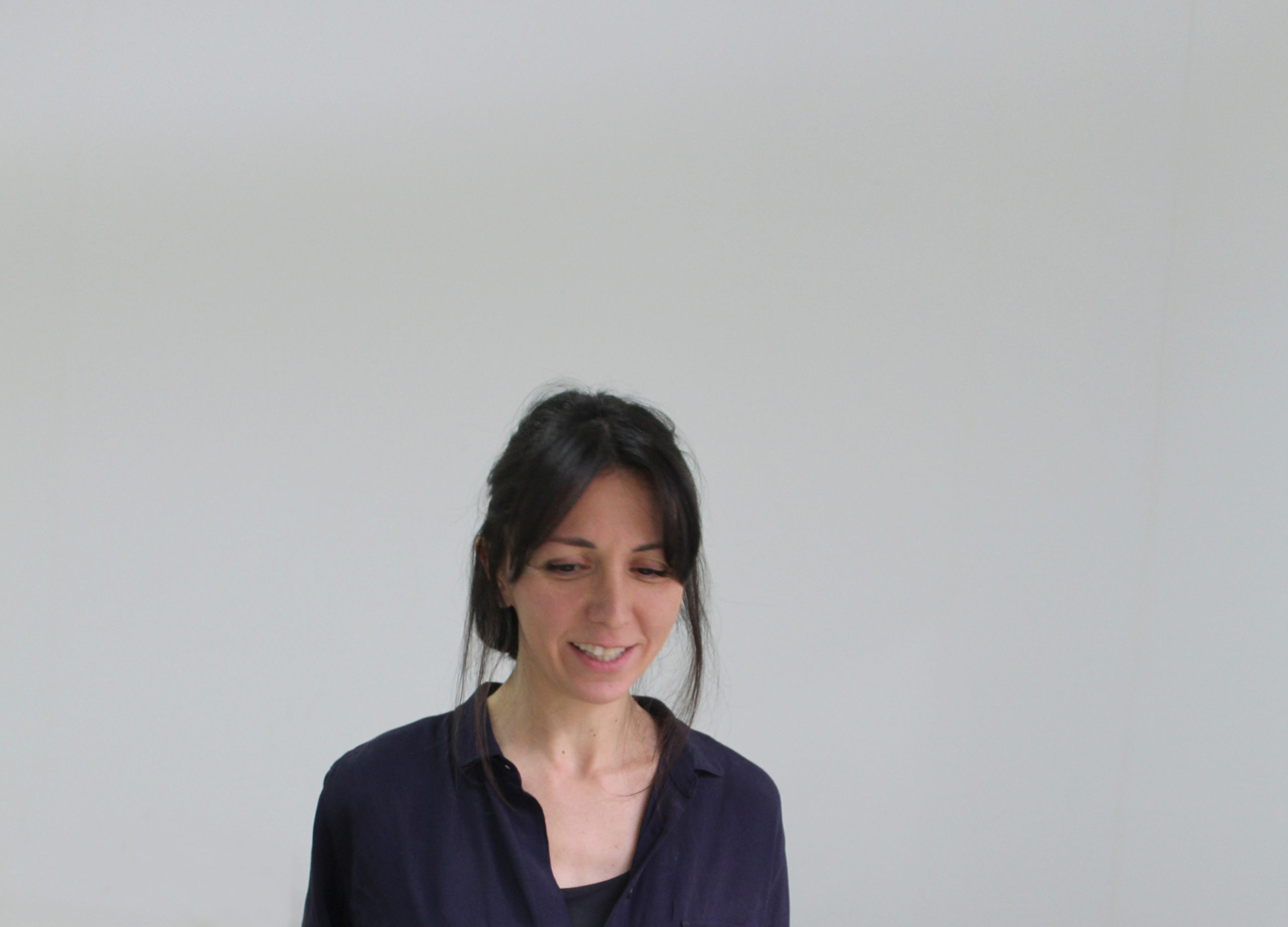 Portrait of Shirin Salehi: she is looking down with a big blank space behind her