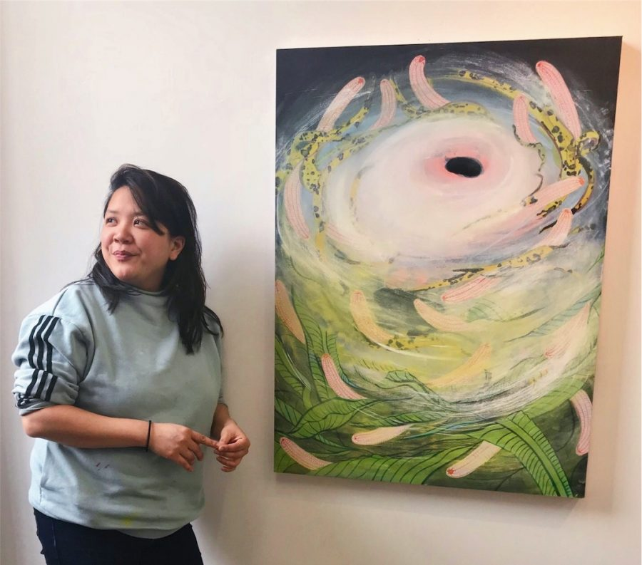 Tammy Nguyen with long black hair stands next to one of her paintings