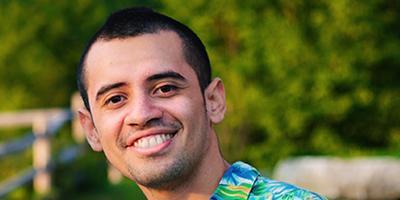 Josue smiles, with buzzed black hair in a Hawaiian shirt