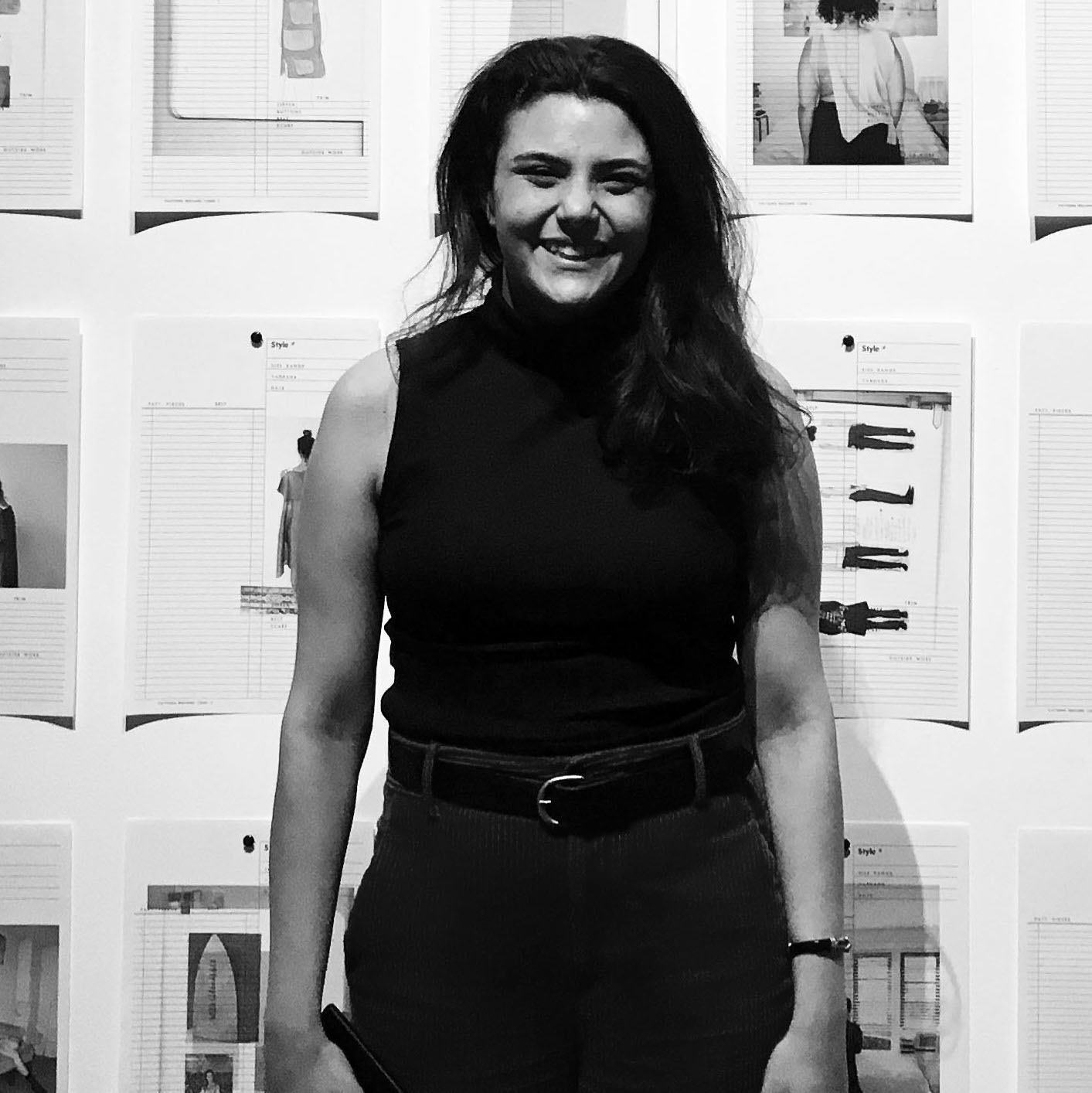 A grayscale photo of a woman standing in front of prints on a wall
