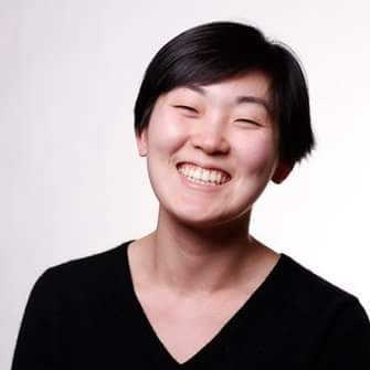 Myong Jin smiles with short, straight black hair