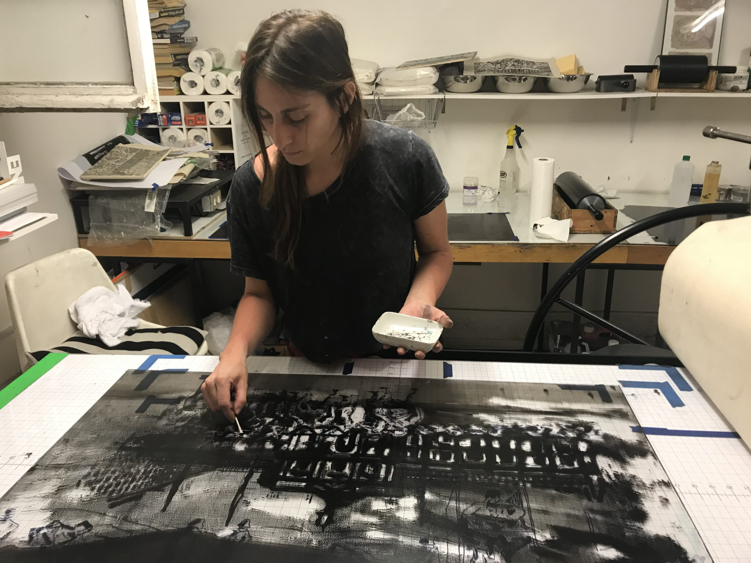 Maria Veronica San Martin is pictured leaning over a press inking/prepping a plate for a print.